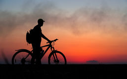 Silhouette of cyclist on the background of red sunset. Biker with bicycle on the field during sunrise Stock Photo