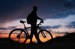 Silhouette of cyclist on the background of sunset. Biker with bicycle on the sand during sunrise Royalty Free Stock Photo