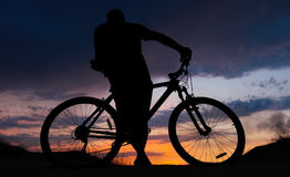 Silhouette of cyclist on the background of sunset. Biker with bicycle on the sand during sunrise Stock Photos
