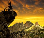 Silhouette of the cyclist on bike at sunset . Stock Photos