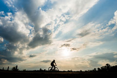 Silhouette of cyclist with friend motion on sunset background Stock Images