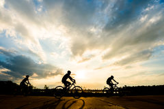 Silhouette of cyclist with friend motion on sunset background Stock Photography