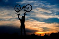 Silhouette of cyclist holding bike above head. Man lifting bicycle in the air on evening sky background. Beautiful evening scenery Stock Photography