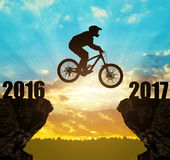 Silhouette cyclist jumping into the New Year 2017. At sunset Stock Photo