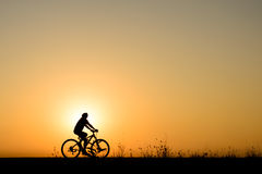 Silhouette of cyclist motion on sunset background Stock Photography