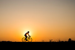Silhouette of cyclist motion on sunset background Stock Images