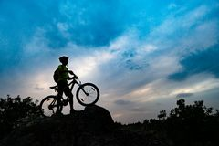 Silhouette of Cyclist with Mountain Bike on Rock at Sunset. Extreme Sports and Enduro Cycling Concept. Silhouette of Cyclist with Mountain Bike on the Rock at royalty free stock photography