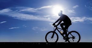Silhouette of the cyclist riding Royalty Free Stock Photos