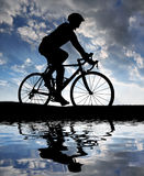 Silhouette of the cyclist. Riding a road bike at sunset Stock Photos