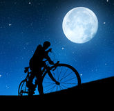 Silhouette of the cyclist. On a road bike in night Royalty Free Stock Photos