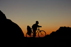 Silhouette of the cyclist on road bike at sunset Royalty Free Stock Images