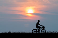 Silhouette of the cyclist on road bike at sunset Stock Photos