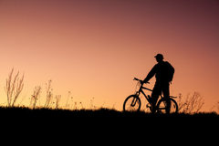 Silhouette of a cyclist with sunset background Stock Image