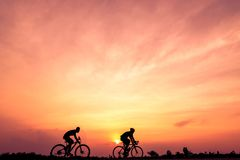 Silhouette of cyclists ride bicycle on sunset background. Two men Ride on bike on the road with orange sky. Sport and active life concept royalty free stock photo