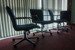 Silhouette dénommée de quatre chaises vides dans le bureau avec des abat-jour de retour Photos stock