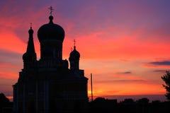 Silhouette d'église avec des dômes contre un coucher du soleil Photos libres de droits