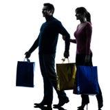 Silhouette d'achats de cadeau de Noël d'homme de femme de couples Photo libre de droits