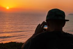 Silhouette d'adolescent dans le coucher du soleil de tir de chapeau avec son smartphone image libre de droits