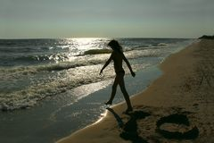 Silhouette d'adolescente sur une plage vide Photo stock