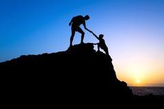 Silhouette d'aide d'homme et de femme en montagnes Images libres de droits