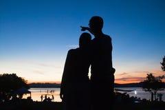 Silhouette d'amant s'étreignant avec le dos crépusculaire de ciel dedans Image libre de droits