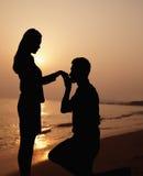 Silhouette d'ami se mettant à genoux et embrassant sa main d'amies sur la plage au coucher du soleil Images libres de droits