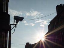 Silhouette d'appareil-photo de télévision en circuit fermé avec le rayon de soleil à travers l'horizon de ville Images libres de droits