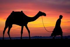 Silhouette d'Arabe avec le chameau au lever de soleil Photo stock