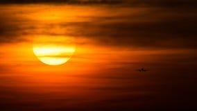 Silhouette d'avion sur le coucher du soleil, approche finale Photos stock