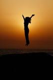 Silhouette d'enfant branchant dans le coucher du soleil Image stock