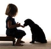 Silhouette d'enfant en bas âge alimentant son chiot Image stock