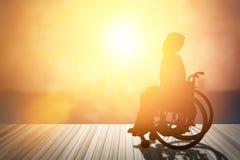 Silhouette d'handicapé sur le fauteuil roulant ou le fond jour des Di Images stock