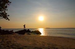 Silhouette d'homme à la plage sur le coucher du soleil Photos stock