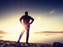 Silhouette d'homme actif s'exerçant et s'étendant sur la plage de lac au lever de soleil photo stock