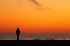 Silhouette d'homme avec l'océan au coucher du soleil Photos libres de droits