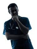 Silhouette d'homme de docteur pensant la verticale songeuse Photographie stock