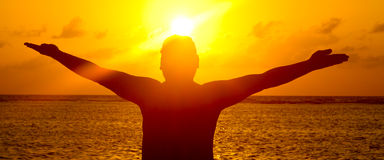 Silhouette d'homme des bras tendus dans le coucher du soleil Images stock