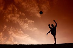 Silhouette d'homme du football jouant avec la boule Photos stock