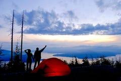 Silhouette d'homme et de femme par la tente rouge avec la vue de l'océan et des îles au lever de soleil Image libre de droits
