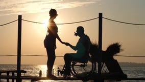 Silhouette d'homme handicapé avec la femme aimée sur la jetée de mer dans la postluminescence de soirée sur le fond du ciel et de banque de vidéos