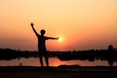 Silhouette d'homme méconnaissable au coucher du soleil Image libre de droits