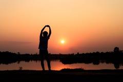 Silhouette d'homme méconnaissable au coucher du soleil Image stock