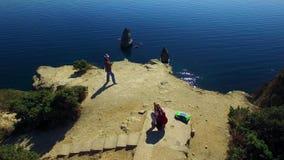 Silhouette d'homme se recroquevillant d'affaires Deux touristes prenant des photos sur la falaise de Fiolent de cap banque de vidéos