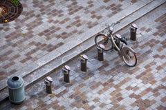 Silhouette d'homme se recroquevillant d'affaires La petite place pavée en cailloutis moderne avec le stationnement fait du vélo,  images libres de droits