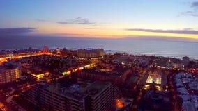 Silhouette d'homme se recroquevillant d'affaires Nuit au-dessus des hôtels côtiers de l'Océan Atlantique Tenerife, ?les Canaries, banque de vidéos