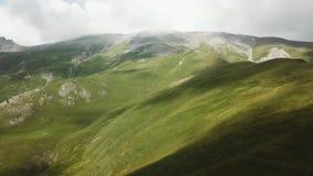 Silhouette d'homme se recroquevillant d'affaires Vol au-dessus de collines rocheuses herbeuses vertes Voler au-dessus des hautes  banque de vidéos