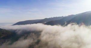 Silhouette d'homme se recroquevillant d'affaires Voler au-dessus des hautes montagnes en beaux nuages Tir d'appareil de photograp banque de vidéos