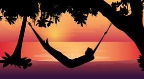 Silhouette d'homme se situant dans des vacances de plage d'hamac Image libre de droits