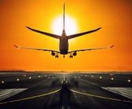 Silhouette d'un avion d'atterrissage à la piste Image stock