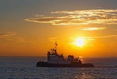 Silhouette d'un bateau de traction subite au coucher du soleil Image stock